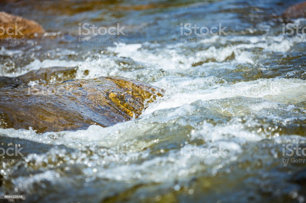 Close-up of stone with water rapids on the river, at travel attraction stock photo