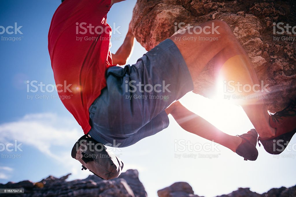 Closeup of strong climber holding to rock overhang with sunflare stock photo