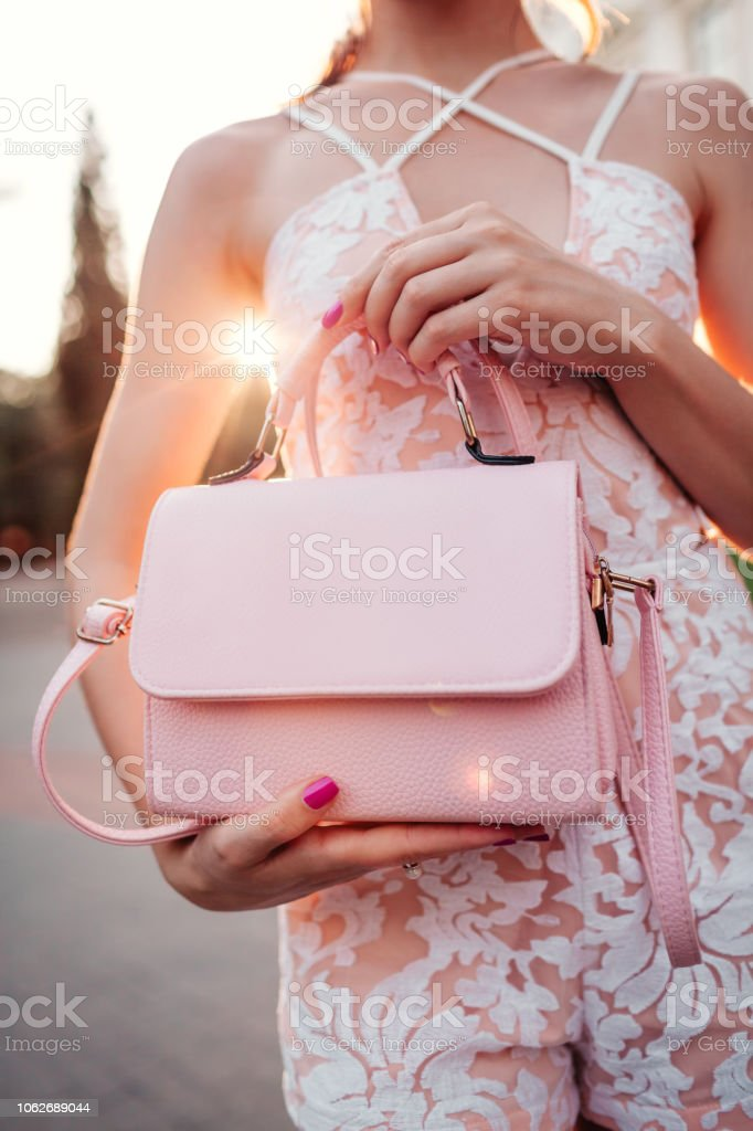 311ce2af Close-up of stylish female handbag. Fashionable woman holding beautiful  accessory and wearing sexy outfit outdoors. - Stock image .