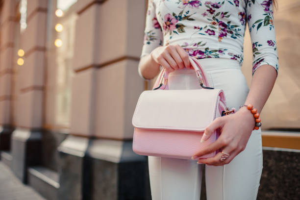 close-up of stylish female handbag. young woman wearing beautiful outfit and accessories outdoors. - borsetta foto e immagini stock