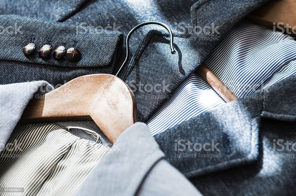 Close-up of suit jackets on hangers in blue colours stock photo
