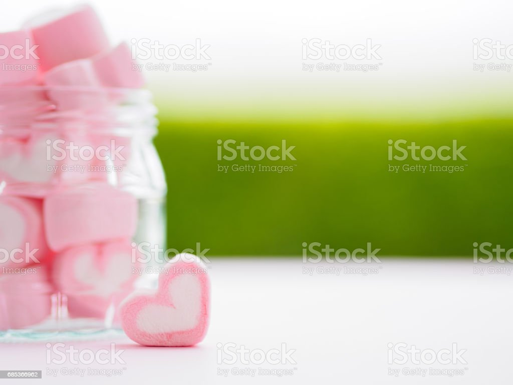 Closeup of sweet marshmallow in the shape of heart on wooden plate and flower at background. foto de stock royalty-free