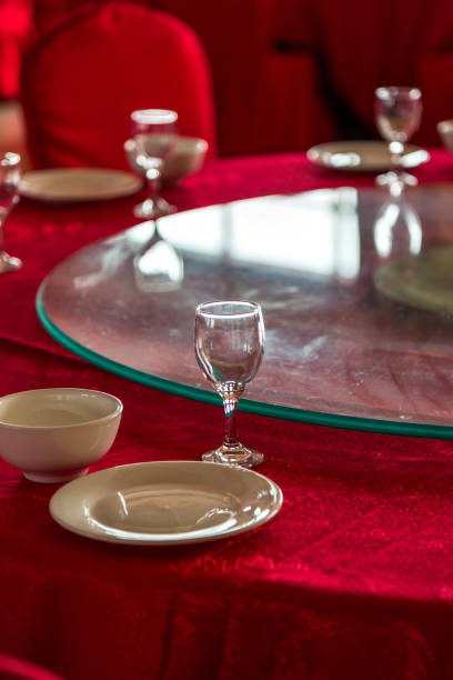 Closeup of table setup with formal dinning placement of plates and liquor glasses. Tables prepared for party or formal celebration of wedding Tables prepared for celebration of wedding chinese wedding dinner stock pictures, royalty-free photos & images