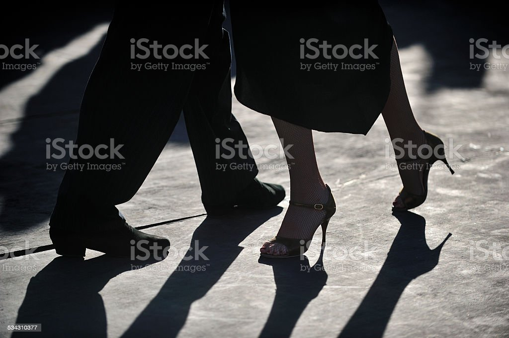 close-up of Tango dancers'€™ foot step in silhouette stock photo