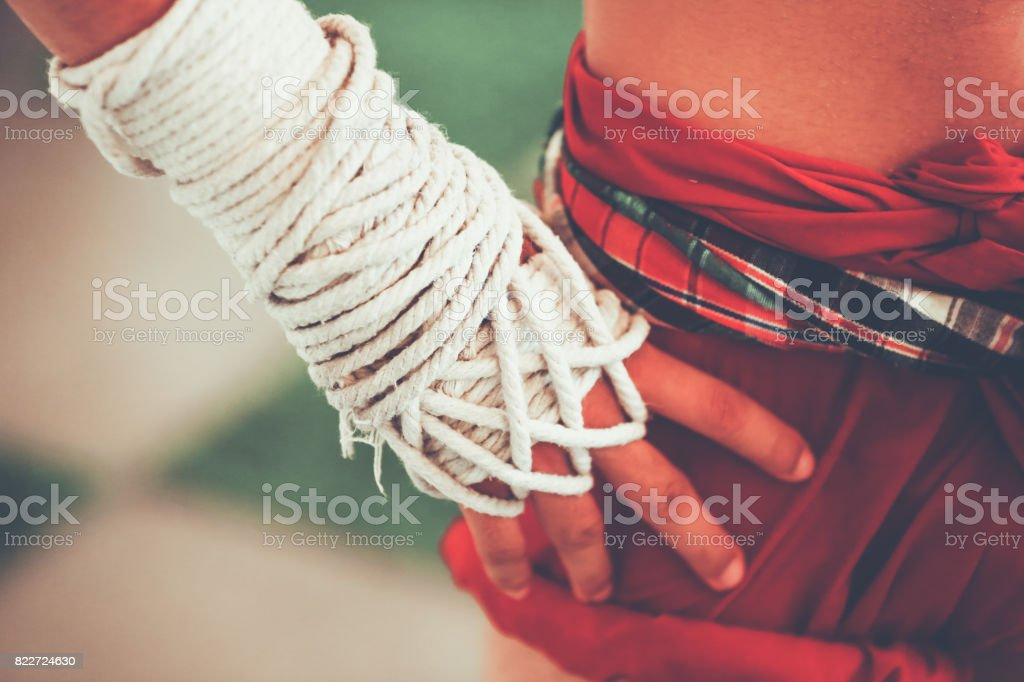 Closeup of tanned muscular Muay Thai fighter preparing and wrapping his hand with traditional hemp cloth stock photo