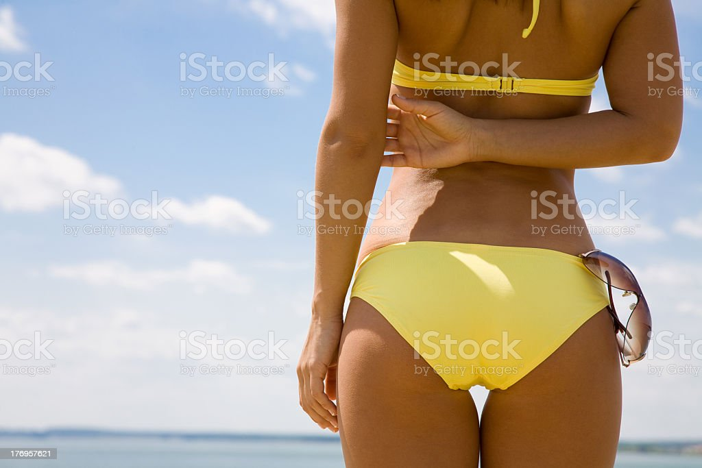 Close-up of tanned woman in yellow bikini facing the ocean royalty-free stock photo