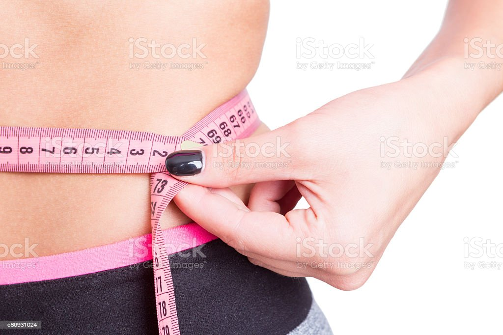 Close-up of tape line around woman waist stock photo