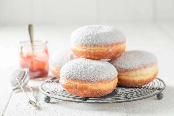Closeup of tasty donuts with powdered sugar on white table stock photo