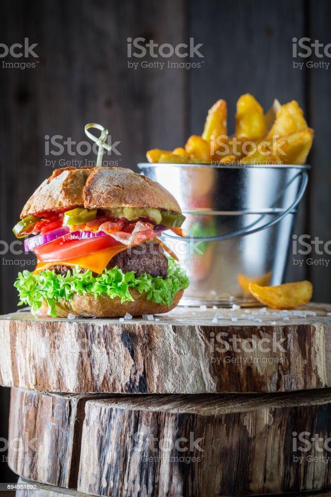 Closeup of tasty hamburger made of bacon, tomato and beef stock photo
