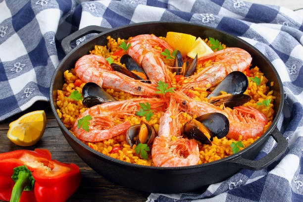 close-up of tasty seafood valencia paella close-up of delicious seafood valencia paella with king prawns, mussels on savory creamy saffron rice with spices and lemon wedges in pan, on wooden table with kitchen towel, view from above arroz stock pictures, royalty-free photos & images
