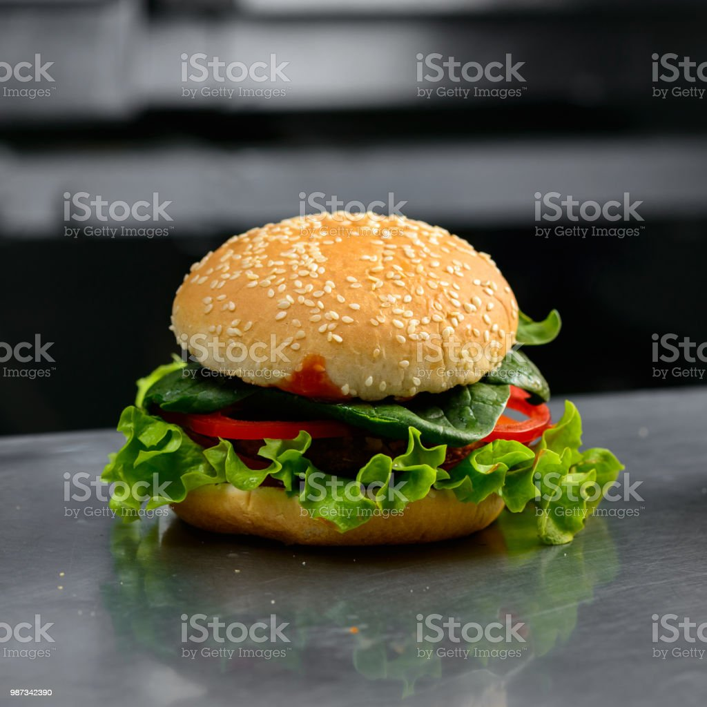 Close-up of tasty veggie quinoa chickpeas burger with tomotoes, stock photo