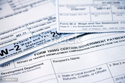 Closeup of overlapping Form 1099G Certain Government Payouts and W-2 forms.