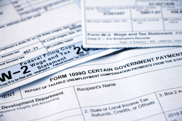 Closeup of tax forms, 1099G and W-2 Closeup of overlapping Form 1099G Certain Government Payouts and W-2 forms. taxes stock pictures, royalty-free photos & images