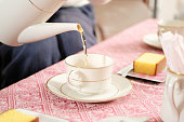 Woman pouring tea to tea cup