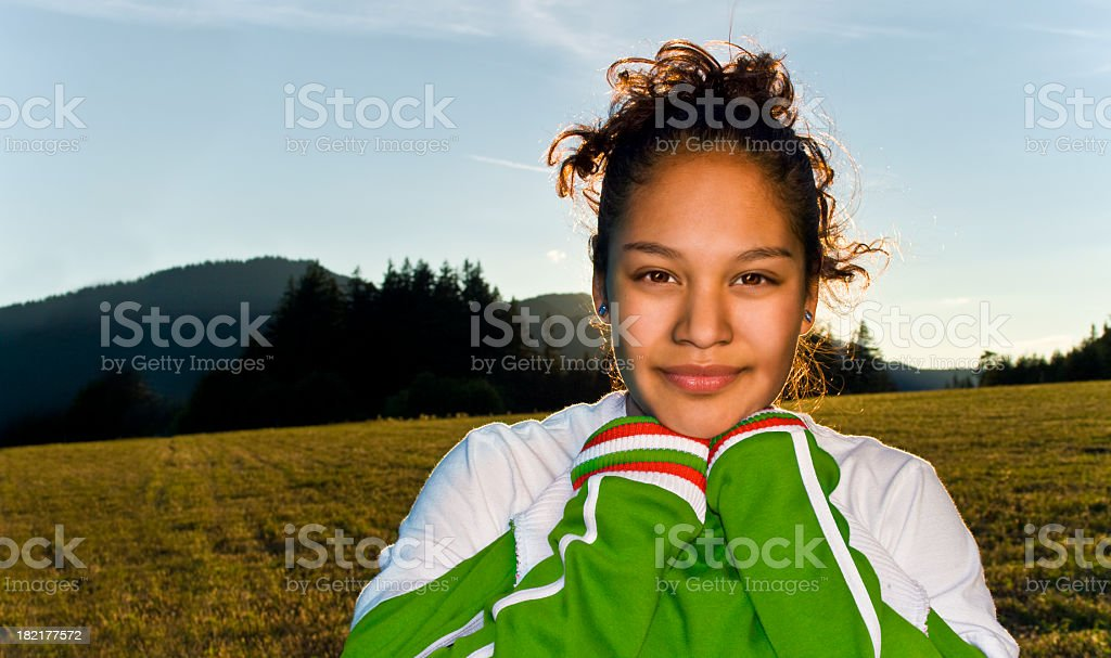 Close-up of teenage girl in sports vest in a field at sunset stock photo