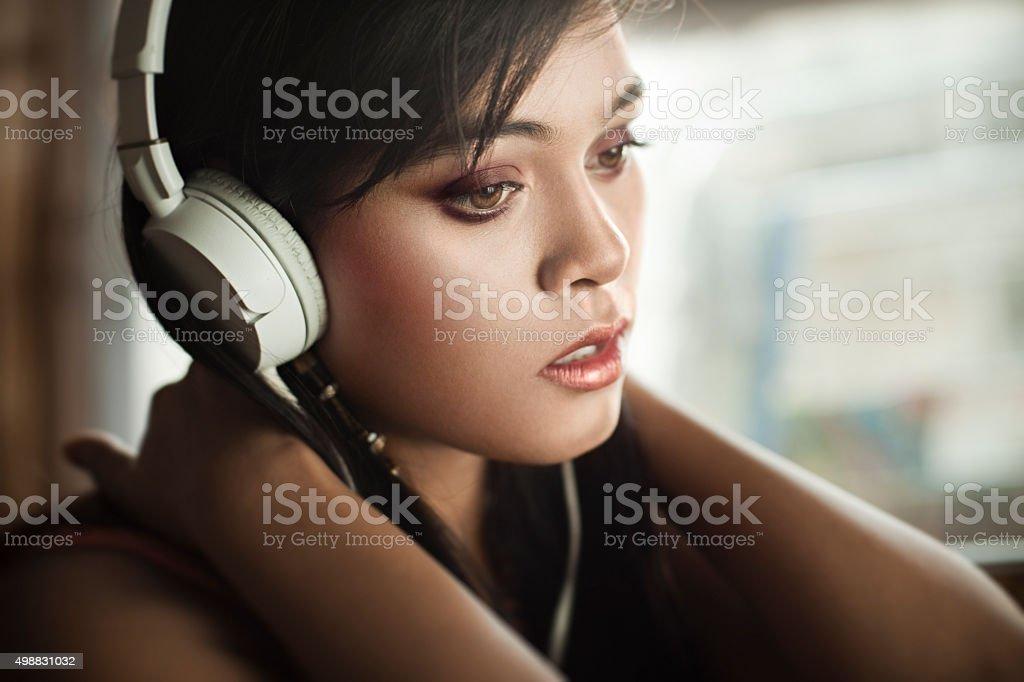 Close-up of teenage Girl listening music through headphones. stock photo