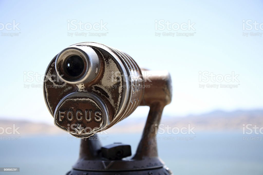Close-up of telescope with defocused coastline in background stock photo