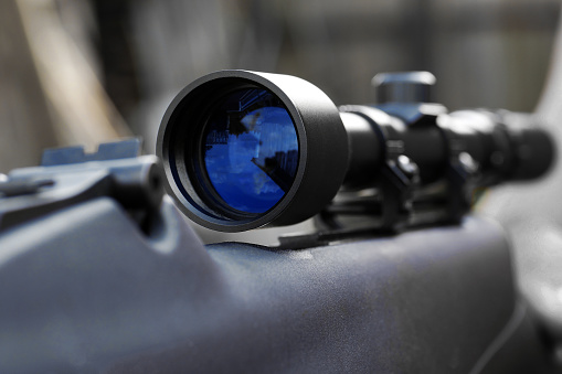 closeup of telescopic sight with reflection in lens mounted on rifle for sniper shooting
