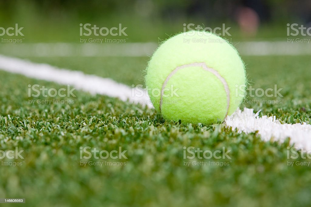 Close-up of tennis ball on white line painted on grass stock photo