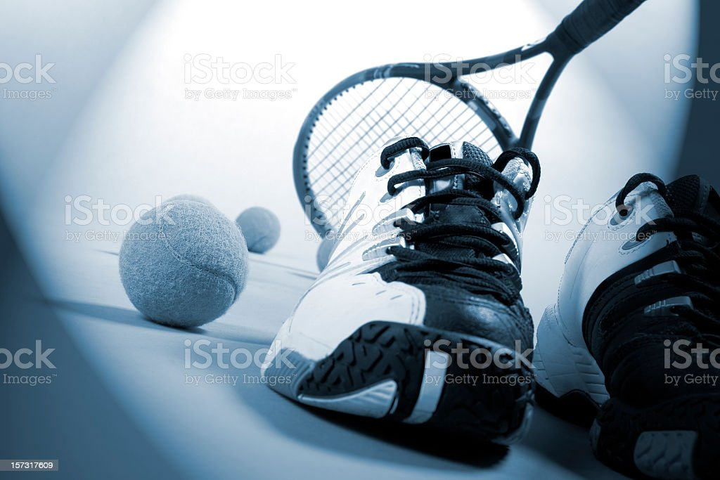 Close-up of tennis balls, tennis racket and shoes, blue toned royalty-free stock photo