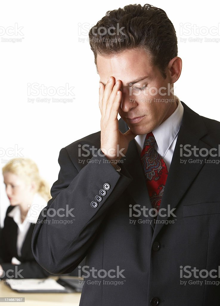 Closeup of tensed businessman with his colleague sitting behind royalty-free stock photo