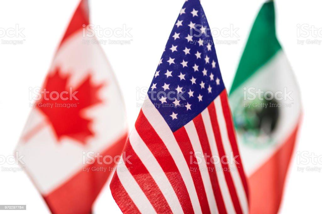 Nahaufnahme der amerikanischen Flagge mit der kanadischen und der mexikanischen Flaggen dahinter auf einem weißen Hintergrund - Konzept Verhandlungen – Foto
