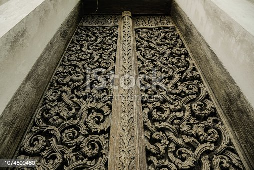 Beautiful masterpiece of the wooden door in the ancient temple of Uttaradit province of Thailand.
