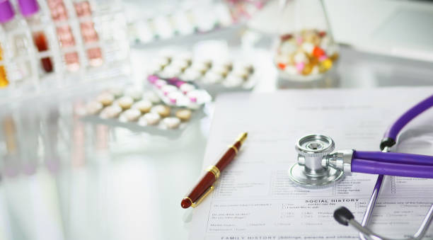 closeup of the desk of a doctors office with a stethoscope in the foreground and a bottle with pills in the background, selective focus – zdjęcie