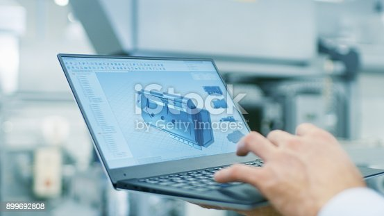 istock Close-up of the Engineer Holding Laptop with CAD Component Model on Screen. In the Background Modern Factory Equipment. 899692808