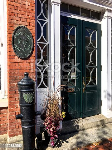 Portsmouth, NH / USA - Oct 16, 2018: Closeup of one of the smoothbore, 1,000 pound cannons, captured from the British by Commodore Perry at The Battle of Lake Erie in 1812, that flank the entrance to the historic Portsmouth Athenaeum. The plaque on the wall memorializes that the Portsmouth Athenæum Society was founded in 1817. The institution's 1805 Federal style building, located on Market Square at the heart of the city, was acquired by the society in 1823.