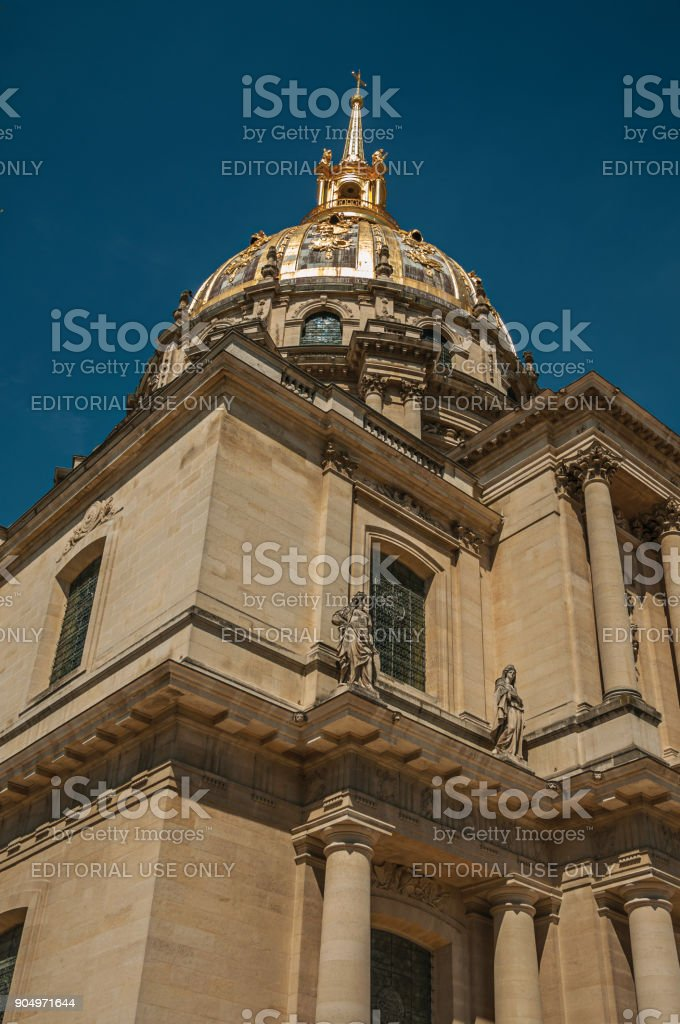 Close-up of the facade and golden dome of Les Invalides Palace with a sunny blue sky at Paris. stock photo