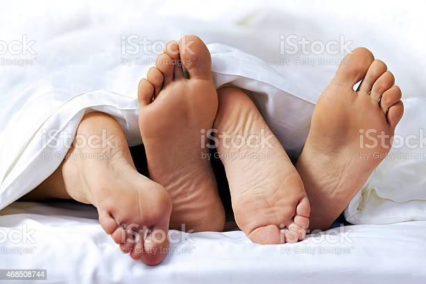 Closeup Of The Feet Of A Couple On The Bed Stock Photo - Download Image Now