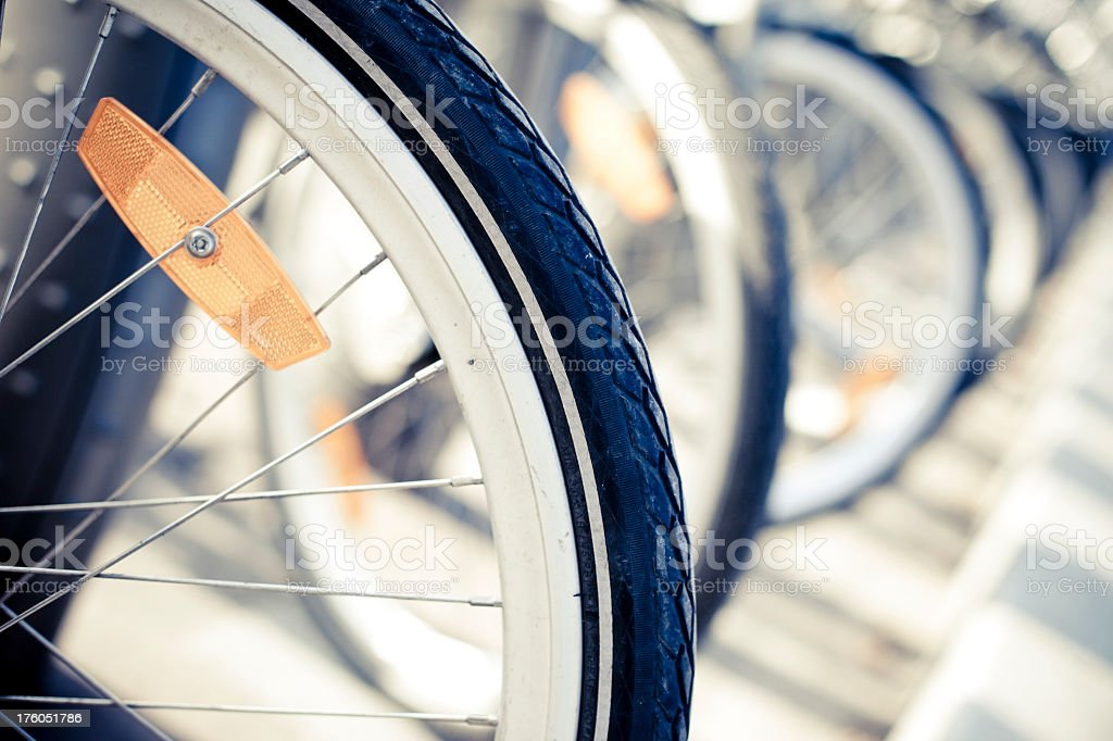 A close-up of the front wheel of a line of bikes royalty-free stock photo
