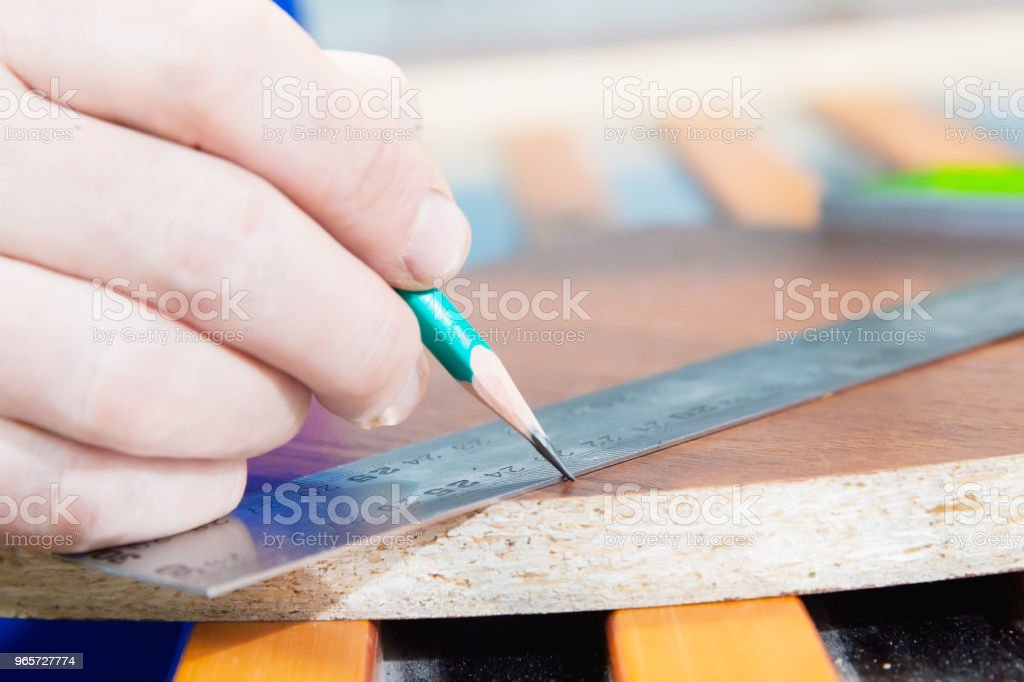 Close-up of the hand of the carpenter's master is marked with a ruler and a pencil blank. The concept of manual furniture production - Royalty-free Adult Stock Photo