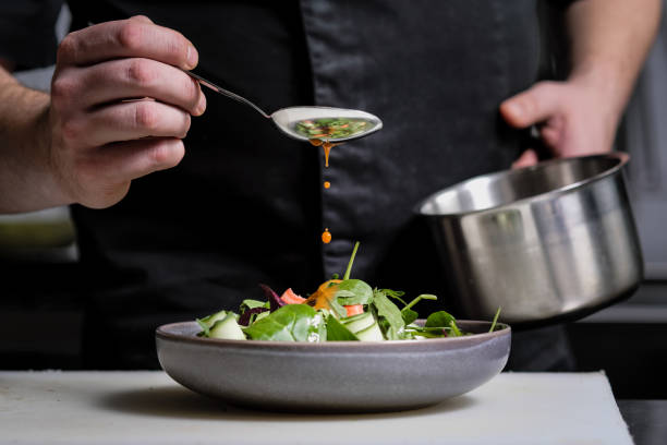 nahaufnahme der hände eines männlichen küchenchefs auf schwarzem hintergrund. soße vom löffel auf die salatschale gießen. - kochkunst stock-fotos und bilder