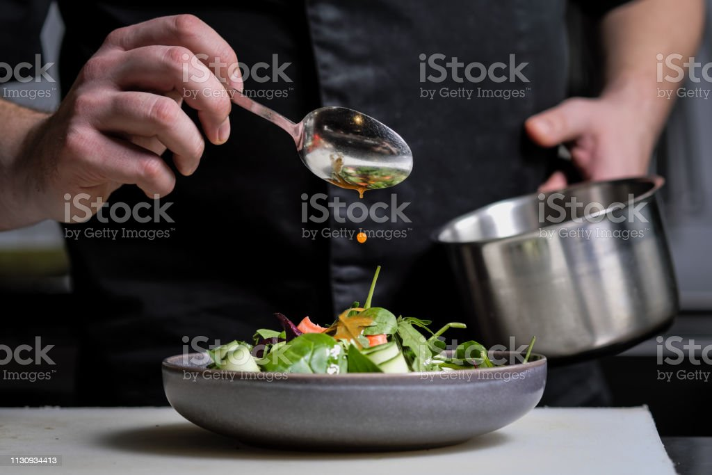 Close-up of the hands of a male chef on a black background. Pour sauce from the spoon on the salad dish. - Foto stock royalty-free di Adulto