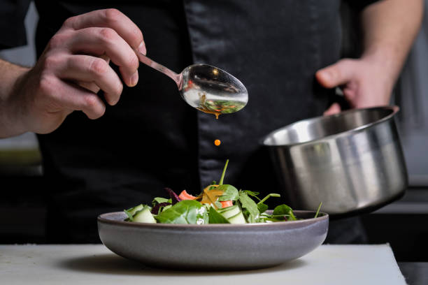 Close-up of the hands of a male chef on a black background. Pour sauce from the spoon on the salad dish. Close-up of the hands of a male chef on a black background. Pour sauce from the spoon on the salad dish. Food decoration. preparing food stock pictures, royalty-free photos & images