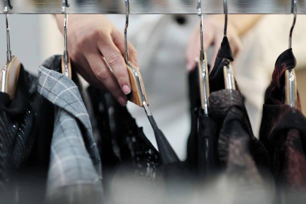 nahaufnahme der hände einer frau, die kleidung auf einem kleiderbügel in einem geschäft auswählt. - geschäftskleidung stock-fotos und bilder