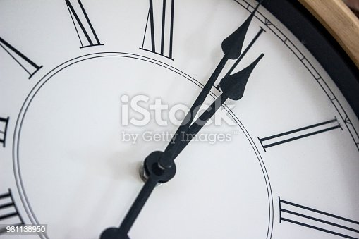 671883446istockphoto Close-up of the hands of a wooden wall clock with roman numerals. 961138950