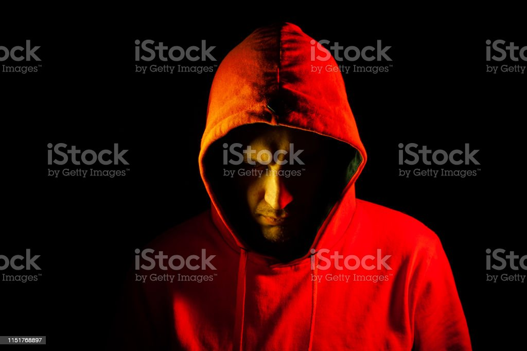 Close-up of the head of a man in an orange hood on the side of the...