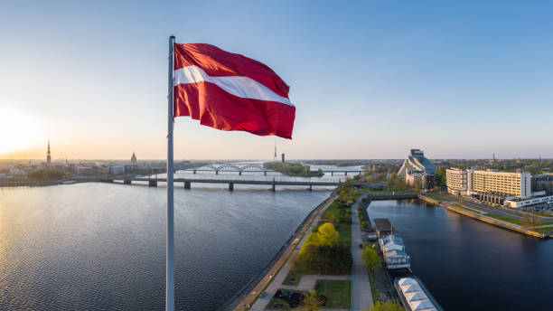 Closeup of the huge flag of Latvia haning above the AB dam in Riga Picture from a drone of the huge Latvian flag above AB dam taken on an early spring morning whilst the sun is rising. River Daugava with it's bridges can be seen on the left. latvia stock pictures, royalty-free photos & images