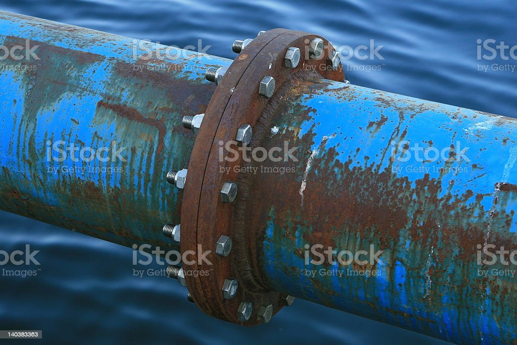 Close-up of the juncture of a rusty pipeline over water stock photo