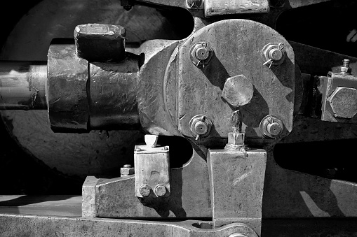 Close up of wheel and coupling rods of an old steam locomotive with textured metal surface and bolts - Black & White Photography