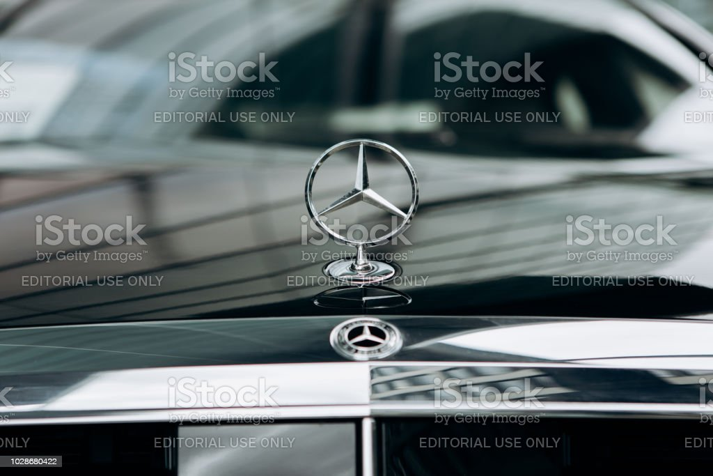 A close-up of the Mercedes sign and the front of the new luxury black Mercedes-Benz car Berlin, August 29, 2018: A close-up of the Mercedes sign and the front of the new luxury black Mercedes-Benz car. Advertisement Stock Photo