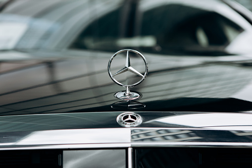 A Closeup Of The Mercedes Sign And The Front Of The New Luxury Black Mercedesbenz Car Stock Photo - Download Image Now
