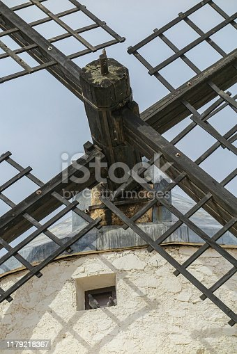 closeup in vertical view of the wooden blade of an old windmill and two doves perched on a little window