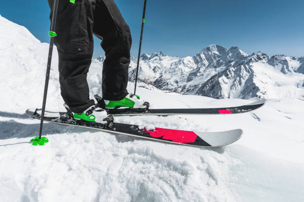 A close-up of the ski on the athlete's feet against the background of snow-capped rocky mountains. The concept of winter sports in the mountains stock photo