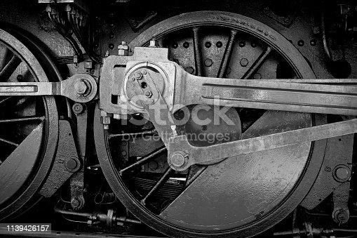 Detail of wheel and coupling rods of an old steam locomotive with textured metal surface and bolts - Black & White Photography