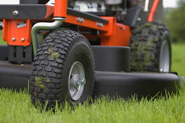 close-up of the wheels and base of a working lawn mower - riding lawn mower stock photos and pictures