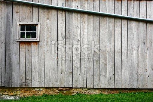 Wood barn side with one window and beautiful stone work.